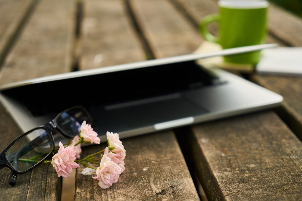 laptop with glasses and flowers